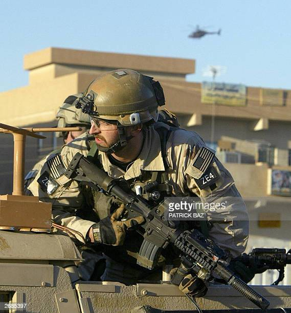 A helicopter flies overhead as US special forces deploy during clashes in Baghdad's western suburb of Abu Gharib 31 October 2003 Four Iraqis...