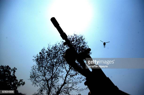 A helicopter flies overhead ready to make a pass if the convoy is ambushed March 1 2005 in the eastern Terai district of Hetauda Nepal The pilots...