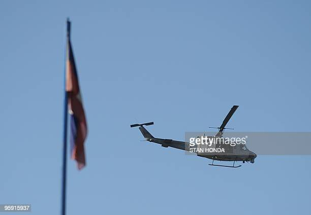 A helicopter flies past the Hatian flag January 21 2010 in Leogane Haiti The United States is now operating at four airports to ferry aid and relief...