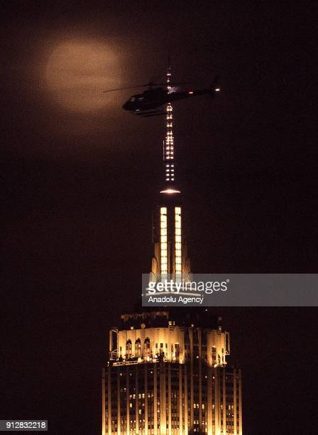 A helicopter flies through the Empire State building as a full moon rises behind the building in New York United States on January 31 2018 The 'Super...