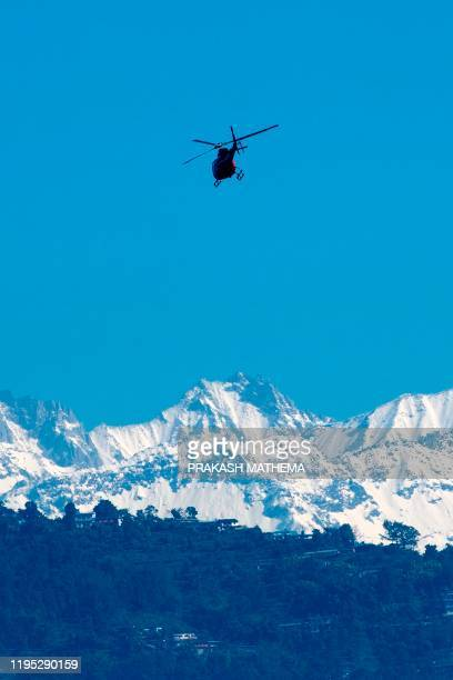 Helicopter flies with rescue team in front of the Annapurna mountain range, in Pokhara, some 200 km west of Kathmandu on January 22, 2020. - Rescuers...
