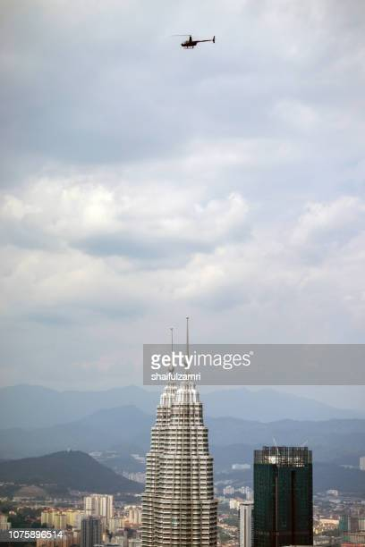 Helicopter fly by over Petronas Twin Towers, a tallest twin towers in Kuala Lumpur, Malaysia.