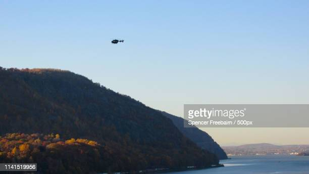 helicopter flying above mountain in sunny day - helicopter photos stock pictures, royalty-free photos & images