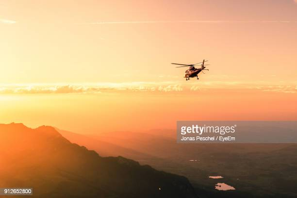Helicopter Flying Against Sky During Sunset