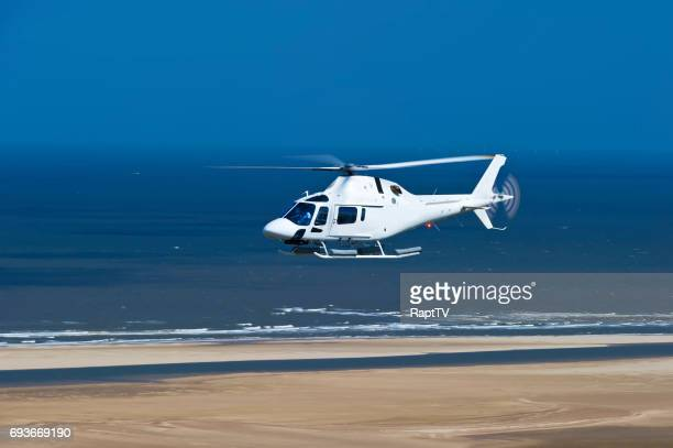 a helicopter flying along a beach and sea. - helicopter rotors stock photos and pictures