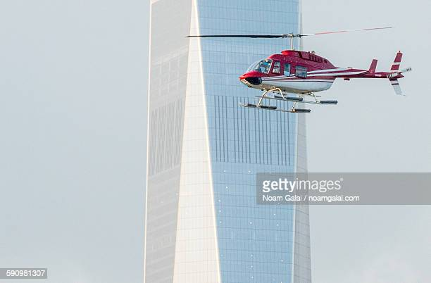 helicopter flying next to skyscraper - noam galai stock pictures, royalty-free photos & images