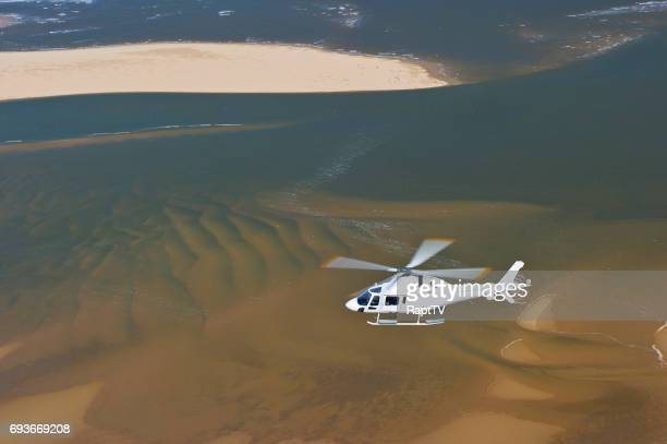 a helicopter flying over a beach and clear blue sea. - helicopter rotors stock photos and pictures