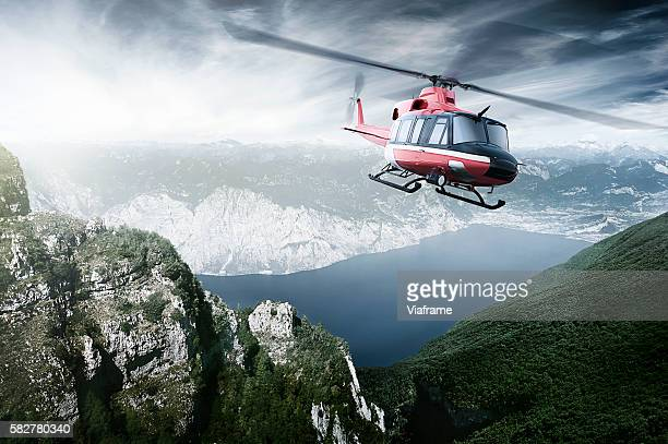Helicopter flying over mountains and a lake