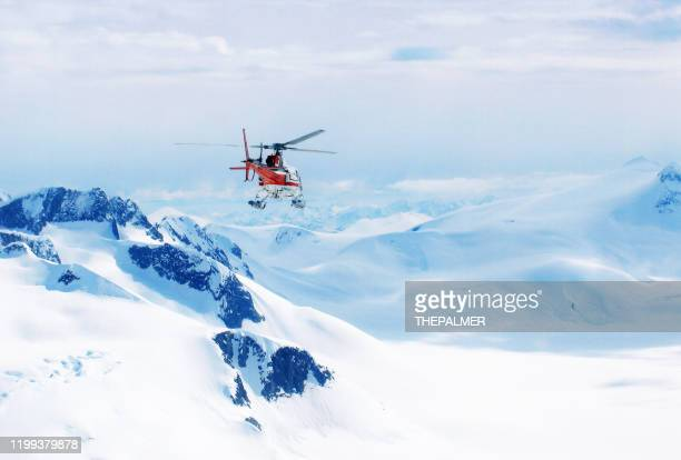 helicopter flying over the mountains in alaska, usa - rescue stock pictures, royalty-free photos & images