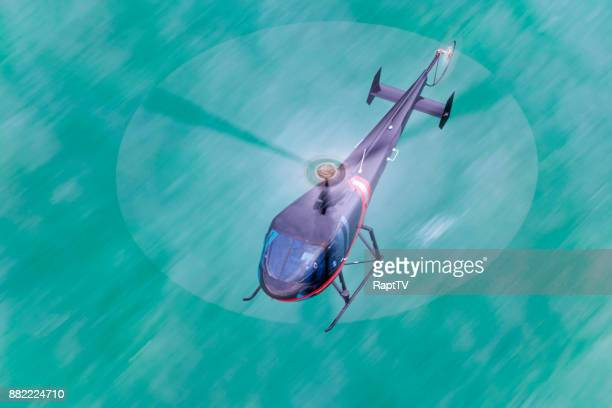 a helicopter flying over the sea with a linked blade. - helicopter rotors stock photos and pictures