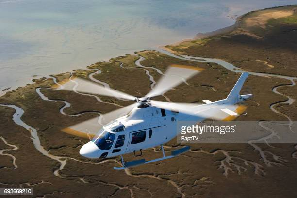 a helicopter flying with blades spinning. - helicopter rotors stock photos and pictures