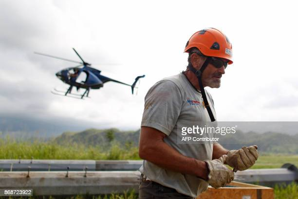 A helicopter from Whitefish Energy Holdings lands on site to pick up workers repairing power line towers after the passing of Hurricane Maria in...