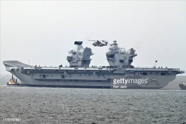 A helicopter hovers above the Royal Navy's newest aircraft carrier HMS Prince of Wales as she sails from the Forth Estuary in heavy rain to begin sea...