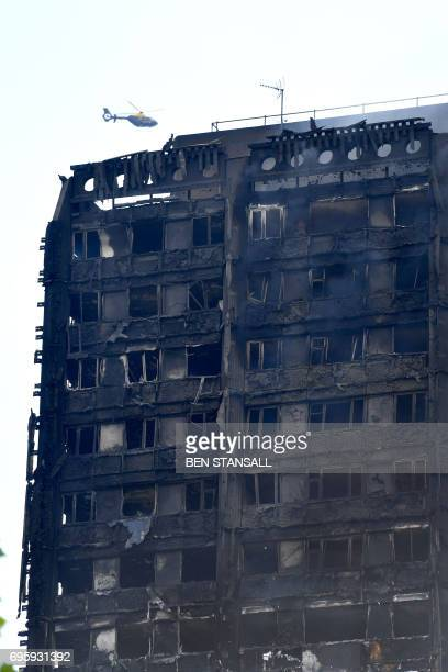 A helicopter hovers near the burntout facade of Grenfell Tower after a fire ripped through the building in west London on June 14 2017 At least six...
