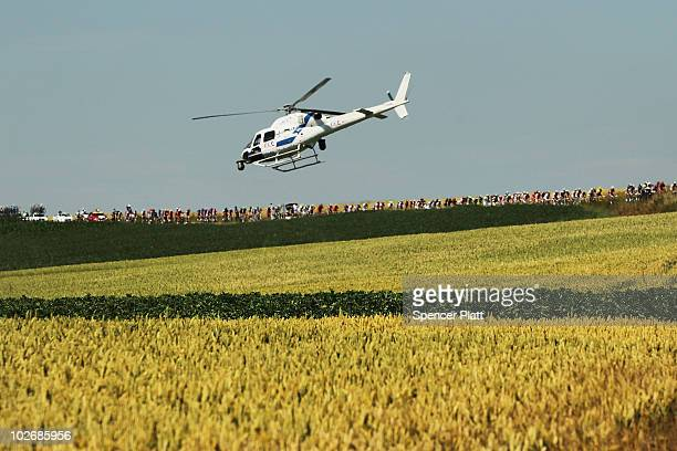 A helicopter hovers over the peloton along the 1535km course in stage four of the Tour de France on July 7 2010 in Reims France A relatively flat...