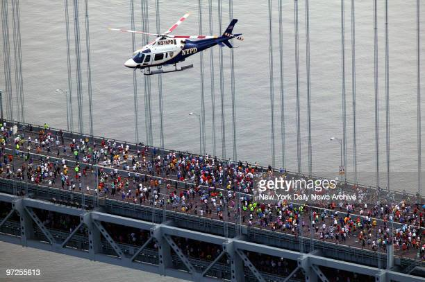 Helicopter hovers overhead as thousands of runners make their way over the VerrazanoNarrows Bridge from Staten Island to Brooklyn during the start of...