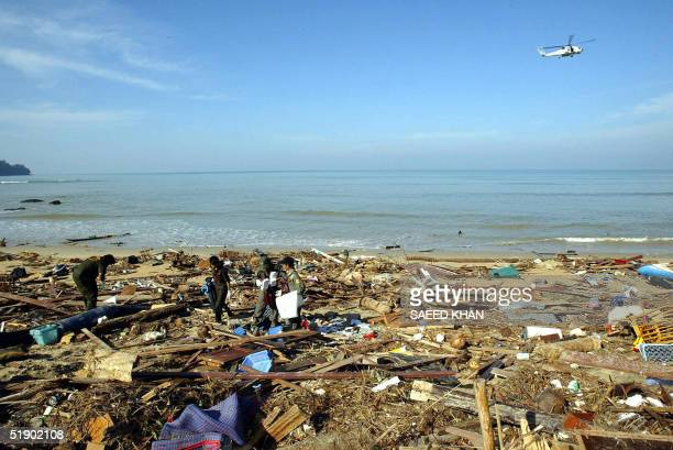 A helicopter howers over the shoreline as rescue workers search for victims through the debris in Khao Lak 30 December 2004 The final death toll from...