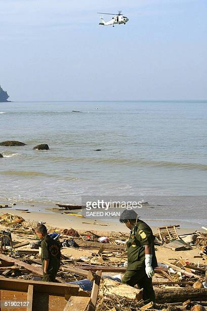 A helicopter howers over the shoreline as rescue workers search for more victims through debris washed away from resorts in Khao Lak 30 December 2004...