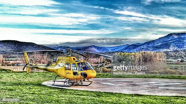 Helicopter In Helipad By Mountains Against Sky