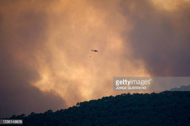 Helicopter is pictured from Benahavis as it overflies a wildfire in Sierra Bermeja mountain range in Malaga province on September 9, 2021. - Almost a...