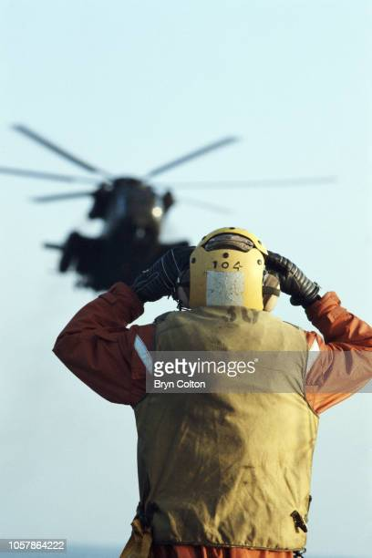 A helicopter is waved off by a crew member from the flight deck of the USS Saipan a Tarawaclass amphibious assault ship of the United States Navy...