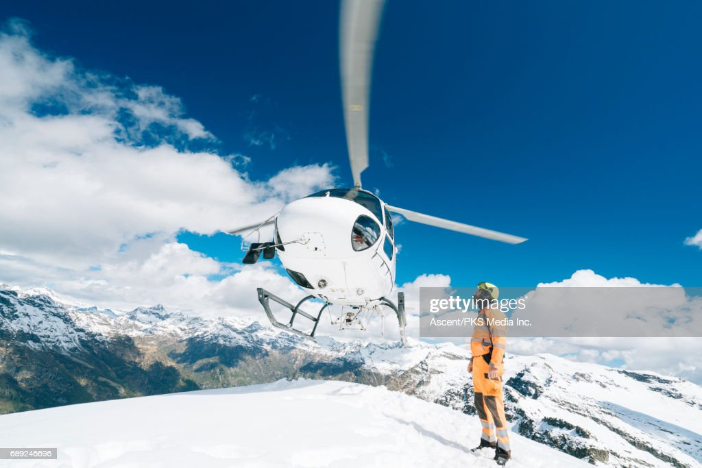 Helicopter lands on mountain summit, ground crew member guides below : Stock Photo