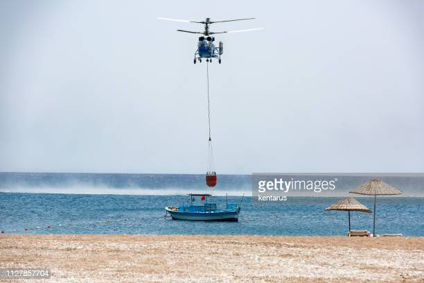 Helicopter loading water from sea to water tank for fire fighting