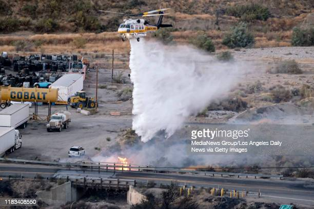 A helicopter makes a drop on fire along Soledad Canyon road in Canyon County early Friday October 25 2019
