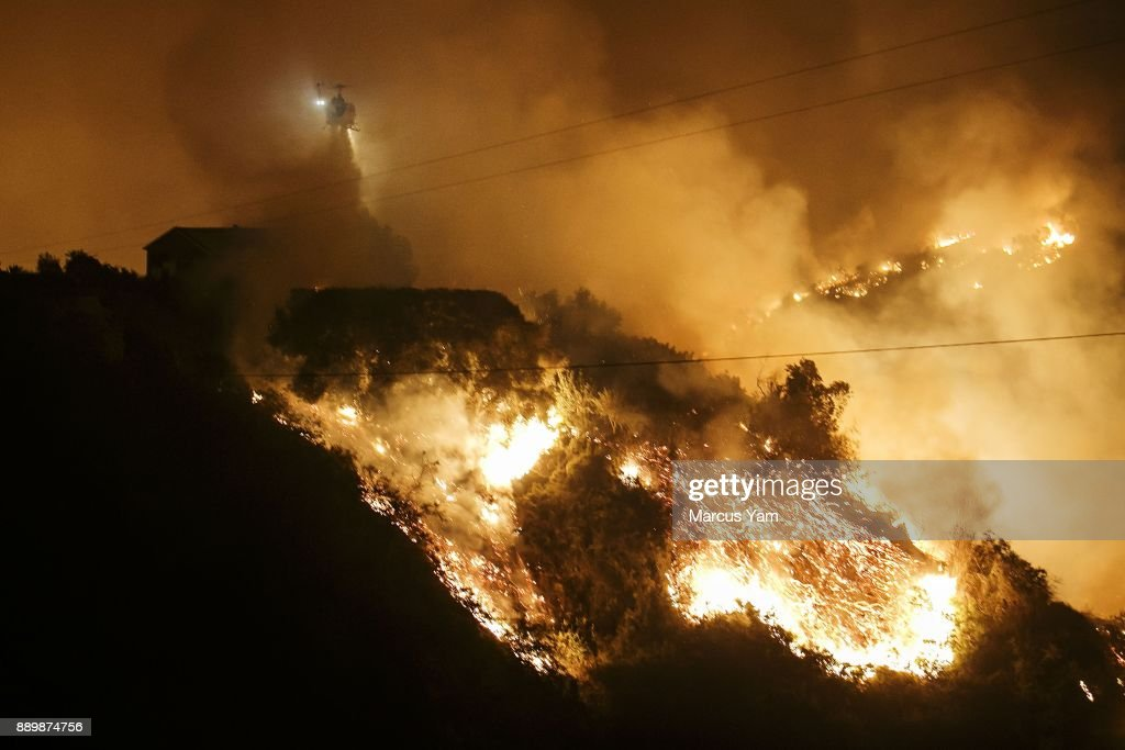 A helicopter makes a water drop as flames make its way up the Shepard Mesa neighborhood, as the Thomas Fire raged out of control overnight, in Carpinteria, Calif., on Dec. 10, 2017.