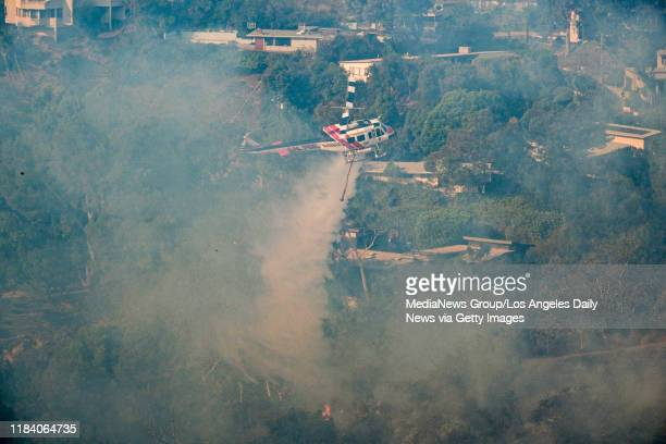 A helicopter makes a water drop in a canyon near the Getty Center at the Getty fire in Los Angeles Monday October 28 2019