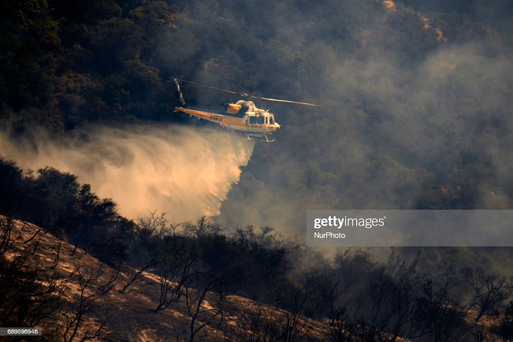 A helicopter makes a water drop on a wildfire in Mandeville Canyon in Los Angeles, California on May 28, 2017. More than 150 firefighters battle the fire that burns near multi-million dollar homes in the Brentwood neighborhood.