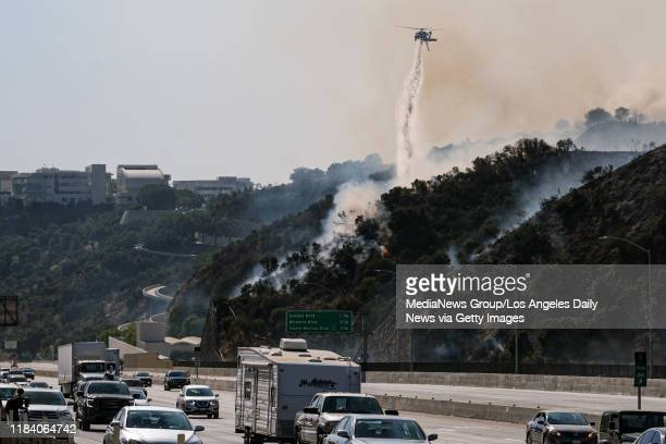 A helicopter makes a water drop on the Getty Fire on hills above the 405 freeway near the Getty Center in Los Angeles Monday October 28 2019