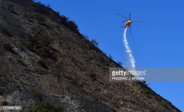 A helicopter makes a water drop over hillsides near in Los Angeles on October 29 2019 More than 1000 firefighters battled a winddriven blaze Monday...