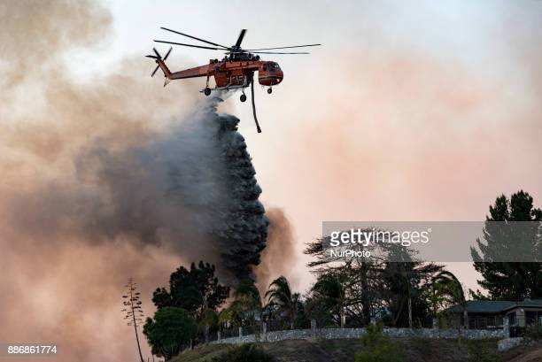 A helicopter makes a water drop over the Creek Fire in Los Angeles California on December 5 2017 The raging fire fueled by strong Santa Ana winds has...