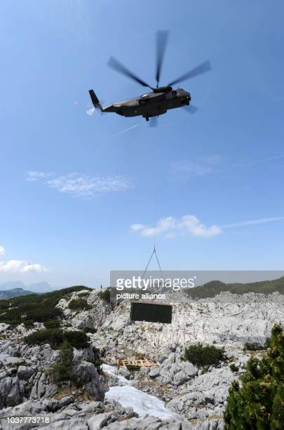 A helicopter of the German Bundeswehr delivers a container to the site the entrance to the Riesending cave on the Untersberg mountain near...