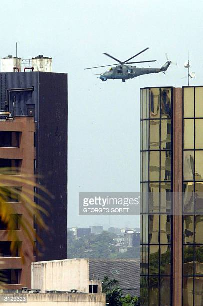 MI24 helicopter of the Ivory Coast ' Air Force hovers at low level over the Plateau district in Abidjan 25 March 2004 as part of boosted security...