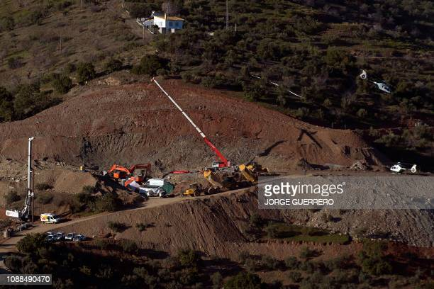 TOPSHOT A helicopter of the Spanish Guardia Civil transporting explosives prepares to land at the site where a child fell down a well in Totalan...