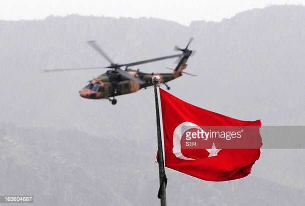 A helicopter of the Turkish army brings back Turkish prisoners over the Habur border crossing in Sirnak on the Turkish side on March 13 2013 after...