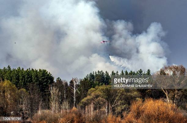 A helicopter of the Ukrainian Emergencies Ministry extinguishes a forest fire burning at a 30kilometer Chernobyl exclusion zone in Ukraine not far...