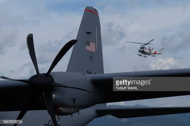 A helicopter operated by Indonesia's Disaster Management Agency flies past a US Air Force's plane delivering aid in Palu Indonesia's Central Sulawesi...