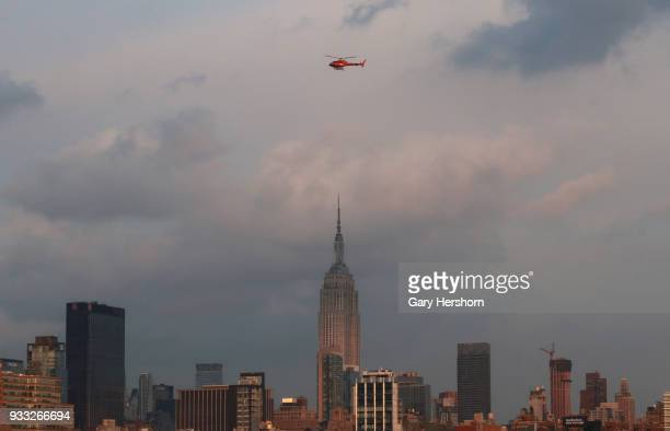 A helicopter owned by Liberty Helicopters flies over the Empire State Building at sunset in New York City on March 15 2018 as seen from Hoboken New...