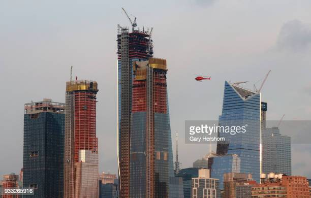 A helicopter owned by Liberty Helicopters flies past Hudson Yards at sunset in New York City on March 15 2018 as seen from Hoboken New Jersey
