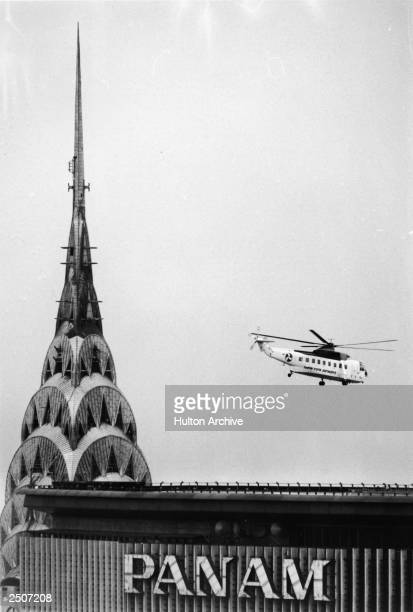 Helicopter passes the art deco spire at the peak of the Chrysler Building and the Pan Am building New York City 1960s
