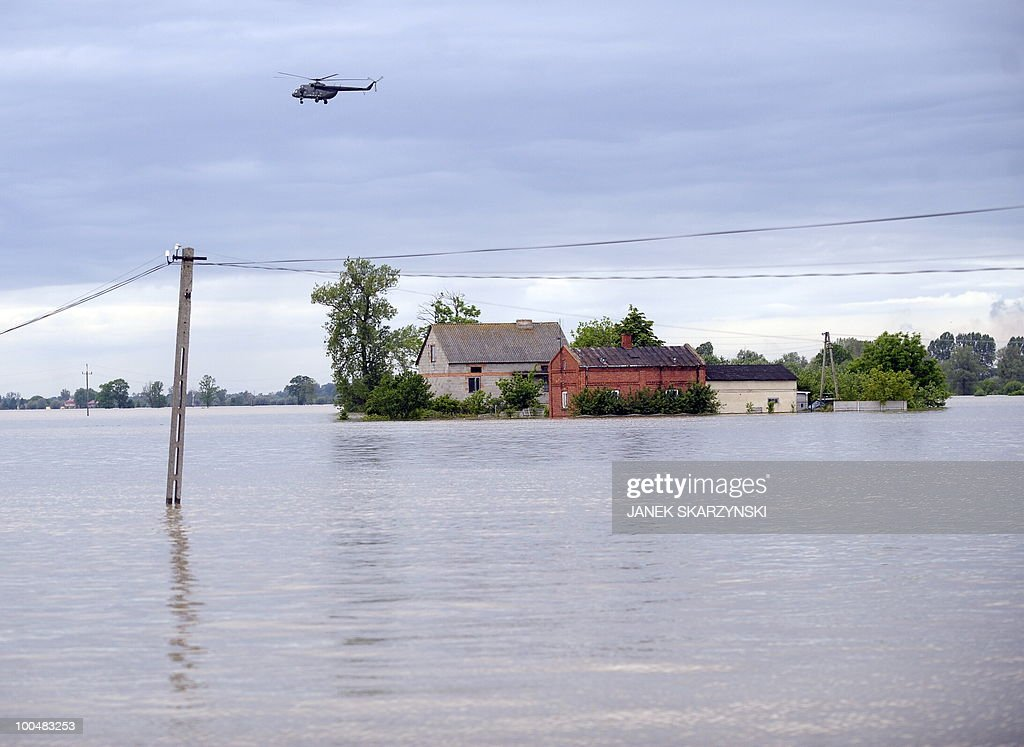 A helicopter patrols flooded Juliszew village in central Poland at Wisla river on May 24, 2010 Flash floods caused by days heavy rainfall have hit parts of central Europe, killing at least 14 people, disrupting power supplies and forcing thousands of people from their homes.