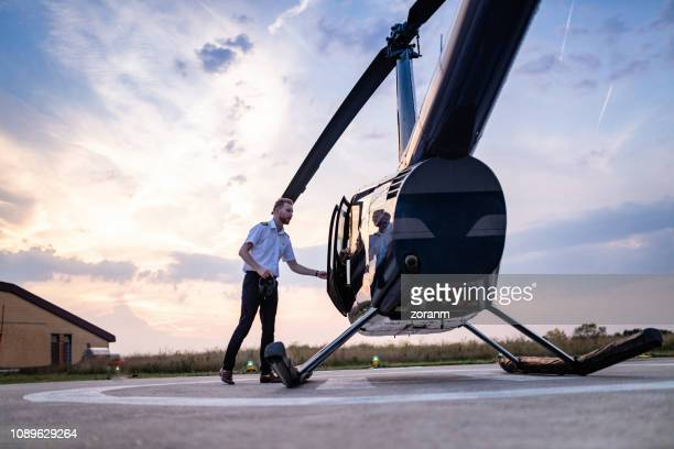 helicopter pilot closing vehicle door - helipad stock photos and pictures
