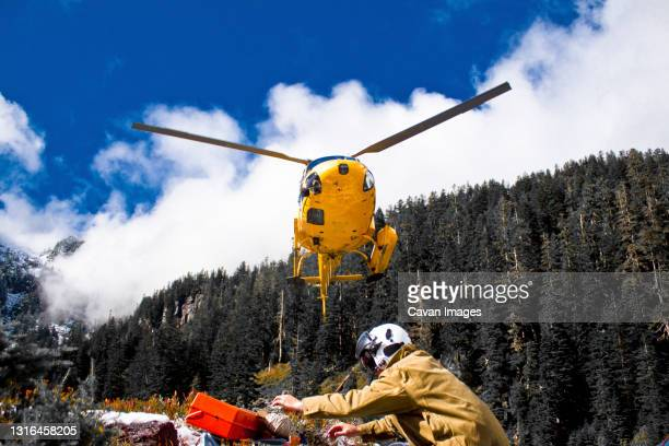 a helicopter prepares to land picking up workers at a remote location. - emergencies and disasters stock pictures, royalty-free photos & images