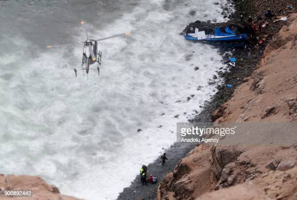 A helicopter prepares to land to transfer a dead body after a bus plunges off the cliff following a collision with a tractor in Lima Peru on January...
