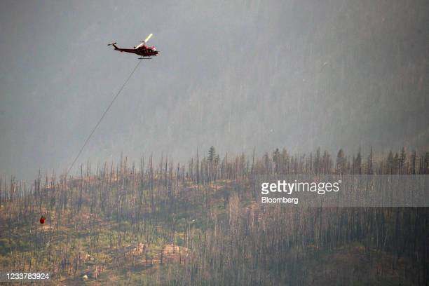 Helicopter prepares to make a water drop along the Fraser River Valley near Lytton, British Columbia, Canada, on Friday, July 2, 2021. A protracted...