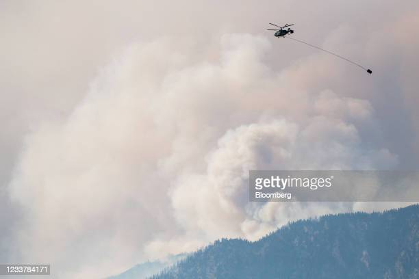 Helicopter prepares to make a water drop as smoke billows along the Fraser River Valley near Lytton, British Columbia, Canada, on Friday, July 2,...