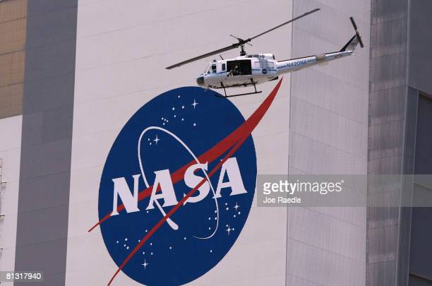 Helicopter provides security for the NASA astronauts as they are driven in in their AstroVan to the space shuttle Discovery on launch pad 39A at the...